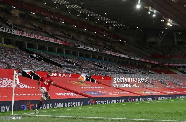 Manchester United's Portuguese midfielder Bruno Fernandes takes a corner kick in front of empty stands during the English Premier League football...