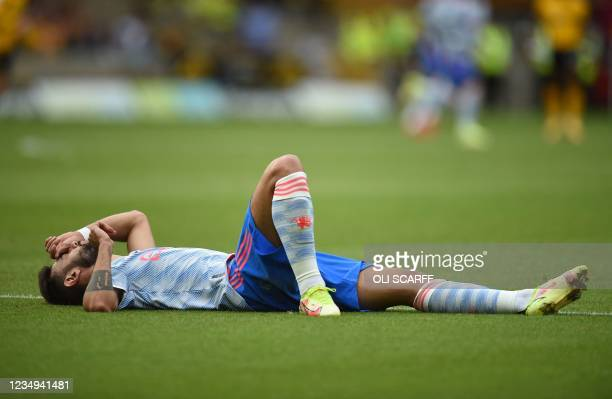 Manchester United's Portuguese midfielder Bruno Fernandes waits for treatment during the English Premier League football match between Wolverhampton...