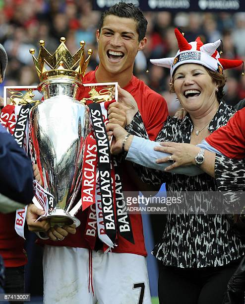 Manchester United's Portuguese midfielder Cristiano Ronaldo celebrates with his mother and the English Premier League trophy after the 0-0 draw with...