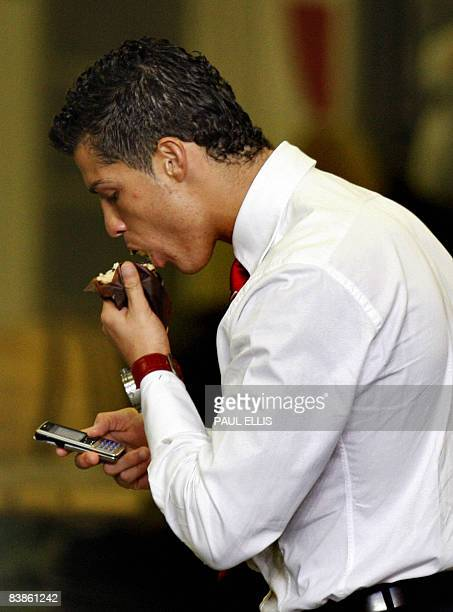 Manchester United's Portuguese midfielder Cristiano Ronaldo eats a muffin after being sent off against Manchester City during their English Premier...