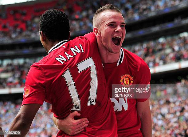 Manchester United's Portuguese midfielder Nani celebrates scoring the third and winning goal with English defender Tom Cleverley during the FA...