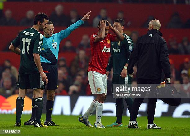 Manchester United's Portuguese midfielder Nani holds his head as Turkish referee Cuneyt Cakir sends him off after a challenge against Real Madrid's...