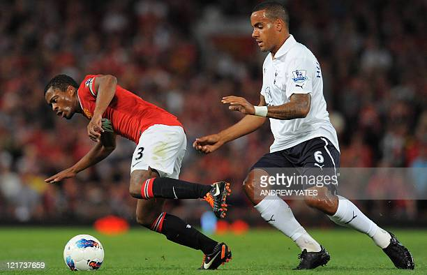 Manchester United's Portuguese midfielder Nani is tackled by Tottenham Hotspur's English midfielder Tom Huddlestone during the English Premier League...