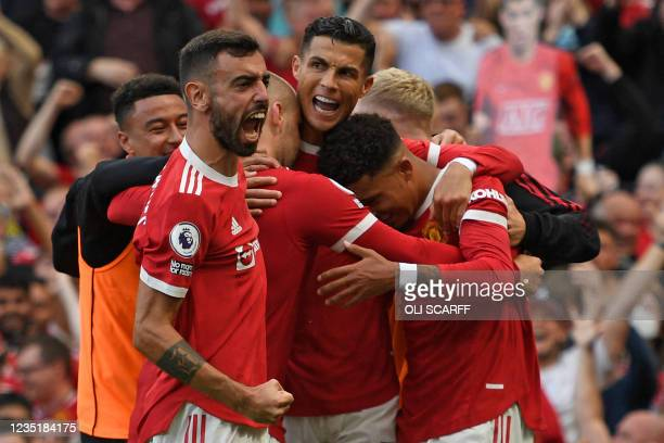 Manchester United's Portuguese striker Cristiano Ronaldo celebrates with teammates after scoring their second goal during the English Premier League...