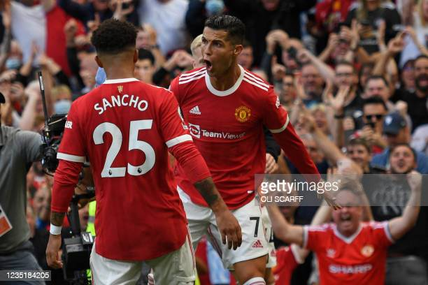Manchester United's Portuguese striker Cristiano Ronaldo celebrates with Manchester United's English striker Jadon Sancho after scoring their second...