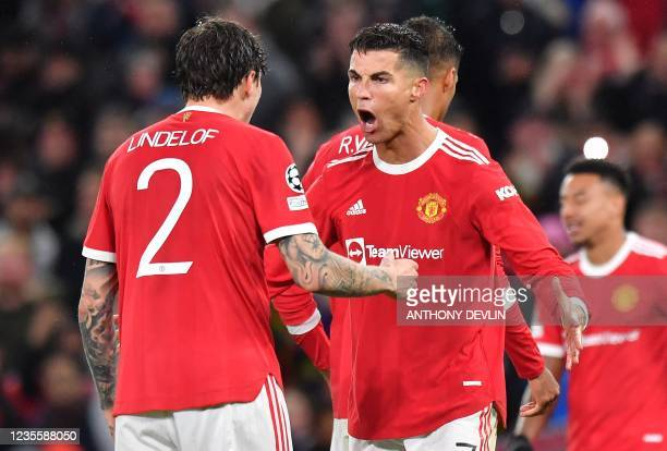 Manchester United's Portuguese striker Cristiano Ronaldo celebrates with Manchester United's Swedish defender Victor Lindelof at the final whistle in...