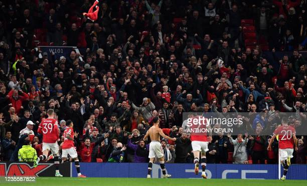 Manchester United's Portuguese striker Cristiano Ronaldo throws his shirt in the air as he celebrates scoring his team's second goal during the UEFA...