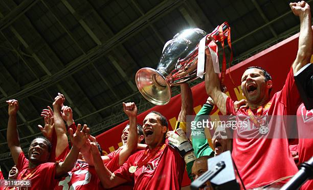Manchester United's Rio Ferdinand and Ryan Giggs hold up the trophy after winning the final of the UEFA Champions League football match against...