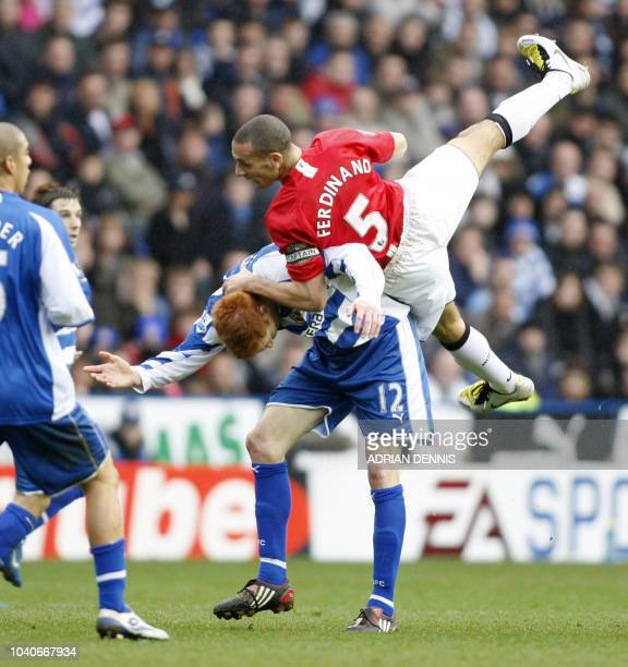 Manchester United's Rio Ferdinand goes over the top of Reading's Dave Kitson during the Premiership football match at the Madejski Stadium in Reading...