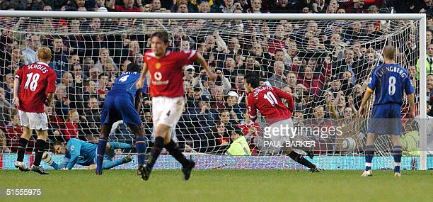 Manchester United's Ruud Van Nistelrooy scores from a penalty kick against Arsenal as teammate Paul Scholes and Arsenal's Patrick Vieira and Freddie...