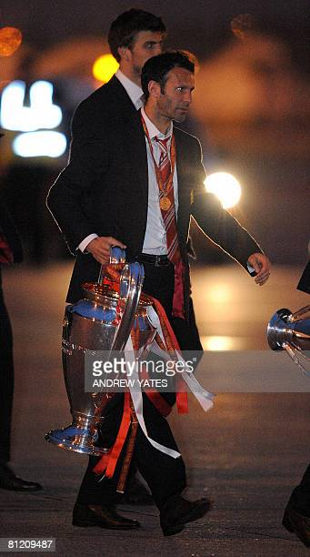 Manchester United's Ryan Giggs holds the Campions League trophy on May 22, 2008 as he returns to Manchester Airport from Moscow after beating Chelsea...