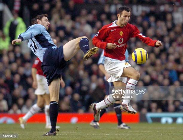 Manchester United's Ryan Giggs skips past a tackle by Southampton's Rory Delap during their Premiership clash at Old Trafford 04 December 2004 No...