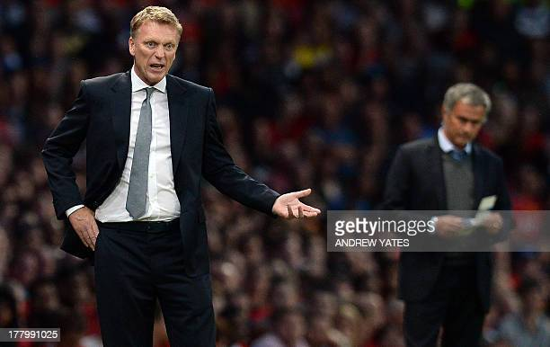 Manchester United's Scottish manager David Moyes gestures as Chelsea's Portuguese manager Jose Mourinho watches during the English Premier League...