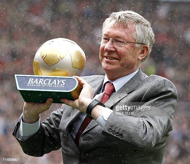 Manchester United's Scottish manager Sir Alex Ferguson holds the manager of the season trophy before the English Premier League football match...