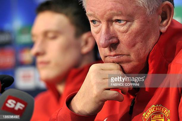 Manchester United's Scottish manager Sir Alex Ferguson next to defender Phil Jones during a press conference in Basel on December 6 on the eve of the...