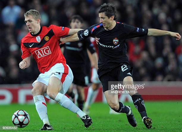 Manchester United's Scottish midfielder Darren Fletcher shields the ball from CSKA Moscow's Russian midfielder Evgeni Aldonin during their UEFA...
