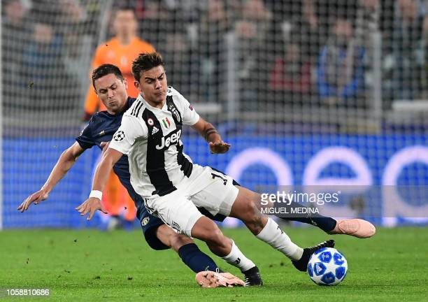 Manchester United's Serbian midfielder Nemanja Matic tackles Juventus' Argentine forward Paulo Dybala during the UEFA Champions League group H...
