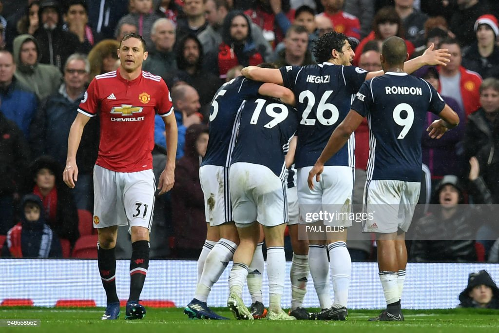 Manchester United's Serbian midfielder Nemanja Matic (L) who's error led to the goal, reacts as West Brom players celebrate their opening goal during the English Premier League football match between Manchester United and West Bomwich Albion at Old Trafford in Manchester, north west England, on April 15, 2018. / AFP PHOTO / Paul ELLIS / RESTRICTED TO EDITORIAL USE. No use with unauthorized audio, video, data, fixture lists, club/league logos or 'live' services. Online in-match use limited to 75 images, no video emulation. No use in betting, games or single club/league/player publications. /