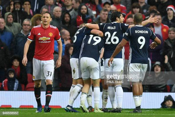 Manchester United's Serbian midfielder Nemanja Matic who's error led to the goal reacts as West Brom players celebrate their opening goal during the...