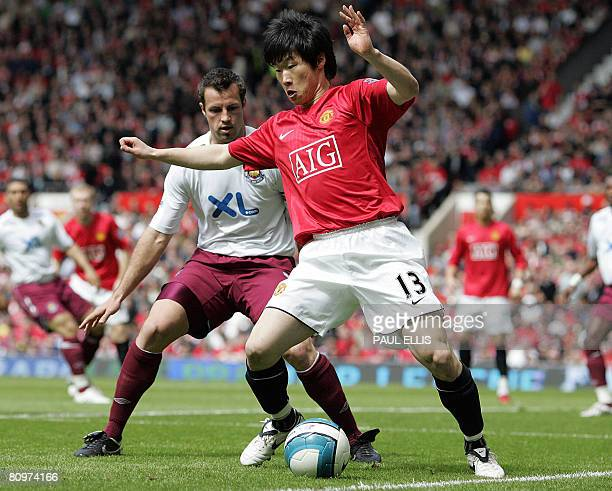 Manchester United's South Korean midfielder Park JiSung shields the ball from West Ham United's Australian defender Lucas Neill during their English...