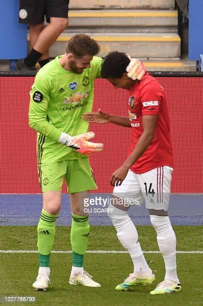 Manchester United's Spanish goalkeeper David de Gea congratulates Manchester United's English midfielder Jesse Lingard after Lingard scored their...