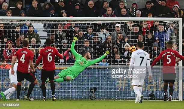 Manchester United's Spanish goalkeeper David de Gea dives but fails to save a shot from Swansea City's Dutch defender Mike van der Hoorn as he scores...