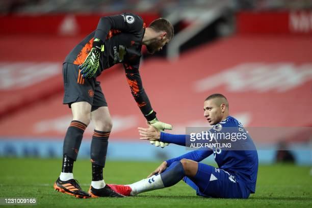 Manchester United's Spanish goalkeeper David de Gea helps up Everton's Brazilian striker Richarlison during the English Premier League football match...