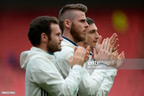 Manchester United's Spanish goalkeeper David de Gea joins the Manchester squad on the pitch to applaud the fans after the end of the English Premier...