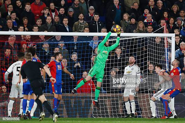 Manchester United's Spanish goalkeeper David de Gea jumps to save the ball during the English Premier League football match between Crystal Palace...