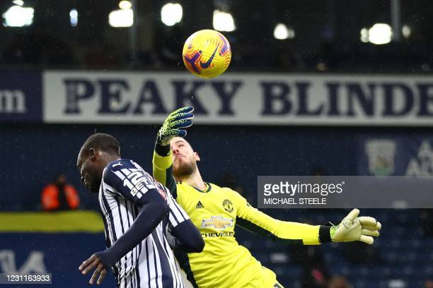 Manchester United's Spanish goalkeeper David de Gea paws the ball away from West Bromwich Albion's Senegalese striker Mbaye Diagne during the English...