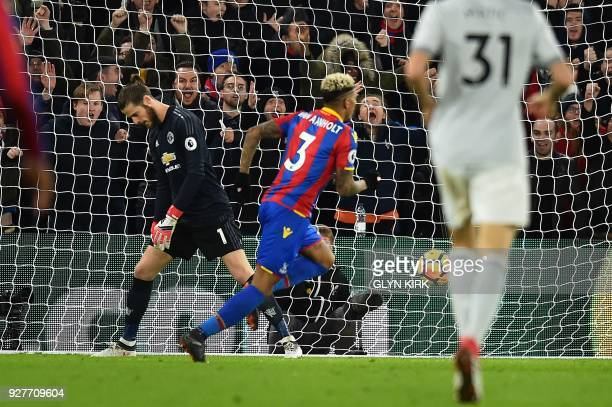 Manchester United's Spanish goalkeeper David de Gea reacts as Crystal Palace's Dutch defender Patrick van Aanholt celebrates scoring his team's...