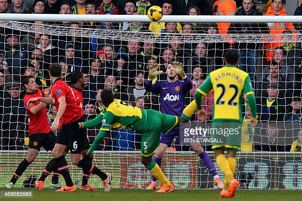 Manchester United's Spanish goalkeeper David de Gea saves a shot on goal from Norwich City's Frenchborn Cameroonian defender Sebastien Bassong during...
