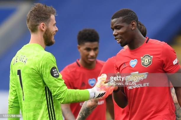 Manchester United's Spanish goalkeeper David de Gea shakes hands with Manchester United's French midfielder Paul Pogba at the end of the English...