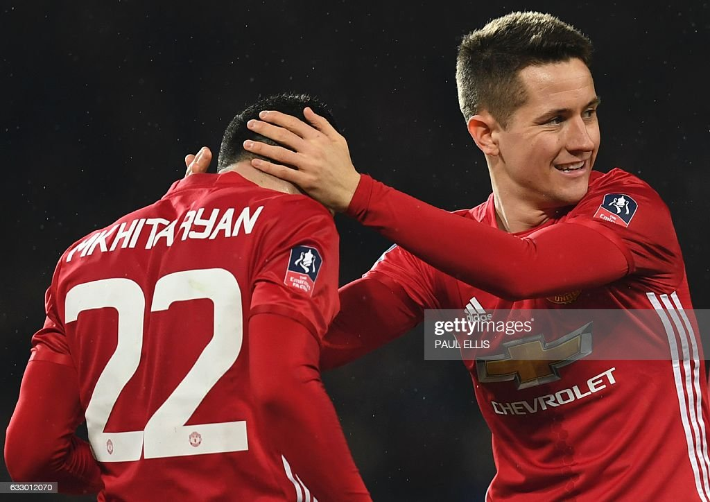 Manchester United's Spanish midfielder Ander Herrera (R) congratulates Manchester United's Armenian midfielder Henrikh Mkhitaryan (L) after Mkhitaryan scored their third goal during the English FA Cup fourth round football match between Manchester United and Wigan Athletic at Old Trafford in Manchester, north west England, on January 29, 2017. / AFP / Paul ELLIS / RESTRICTED TO EDITORIAL USE. No use with unauthorized audio, video, data, fixture lists, club/league logos or 'live' services. Online in-match use limited to 75 images, no video emulation. No use in betting, games or single club/league/player publications. /