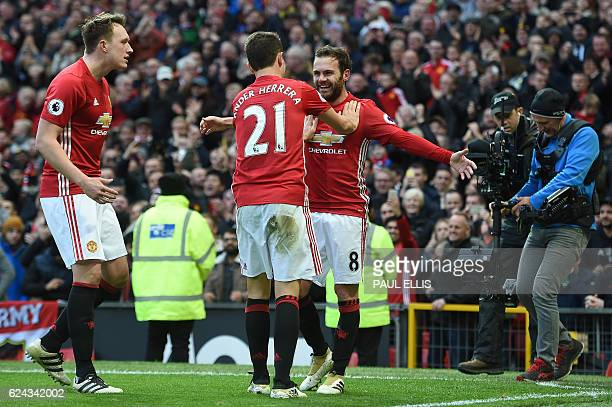Manchester United's Spanish midfielder Juan Mata celebrates scoring his team's first goal with Manchester United's Spanish midfielder Ander Herrera...