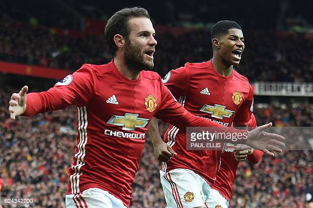 Manchester United's Spanish midfielder Juan Mata celebrates scoring his team's first goal with Manchester United's English striker Marcus Rashford...