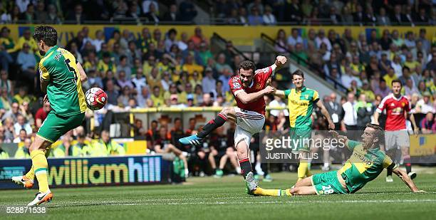 Manchester United's Spanish midfielder Juan Mata shoots but fails to score as Norwich City's English midfielder Gary O'Neil slides in to tackle him...