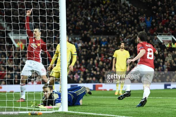 Manchester United's Spanish midfielder Juan Mata turns to celebrate after scoring the opening goal during the UEFA Europa League round of 16...