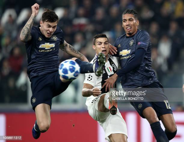 Manchester United's Swedish defender Victor Lindelof Juventus' Portuguese forward Cristiano Ronaldo and Manchester United's English defender Chris...