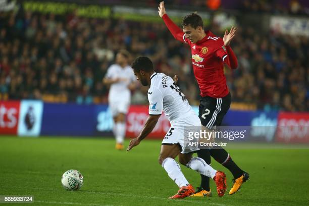 Manchester United's Swedish defender Victor Lindelof vies with Swansea City's English midfielder Wayne Routledge during the English League Cup fourth...