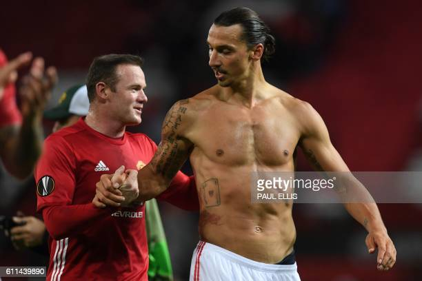TOPSHOT Manchester United's Swedish striker Zlatan Ibrahimovic and Manchester United's English striker Wayne Rooney applaud the fans following the...