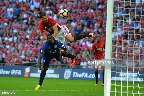 Manchester United's Swedish striker Zlatan Ibrahimovic beats Leicester City's English defender Wes Morgan to head in their second goal during the FA...