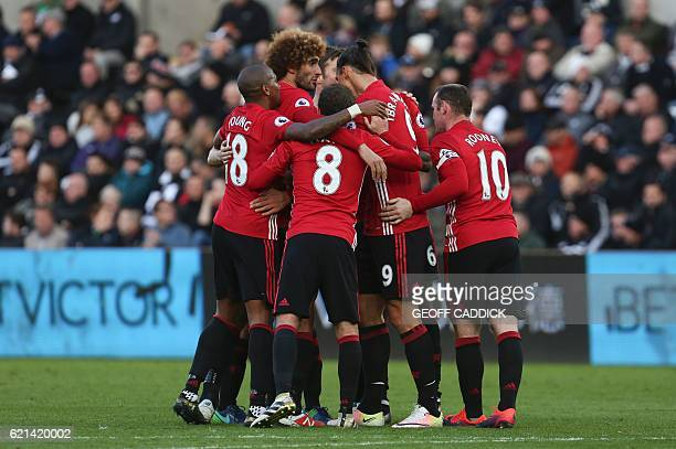 Manchester United's Swedish striker Zlatan Ibrahimovic celebrates scoring his team's third goal with teammates during the English Premier League...