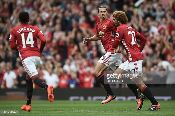Manchester United's Swedish striker Zlatan Ibrahimovic celebrates with Manchester United's Belgian midfielder Marouane Fellaini after he scores their...