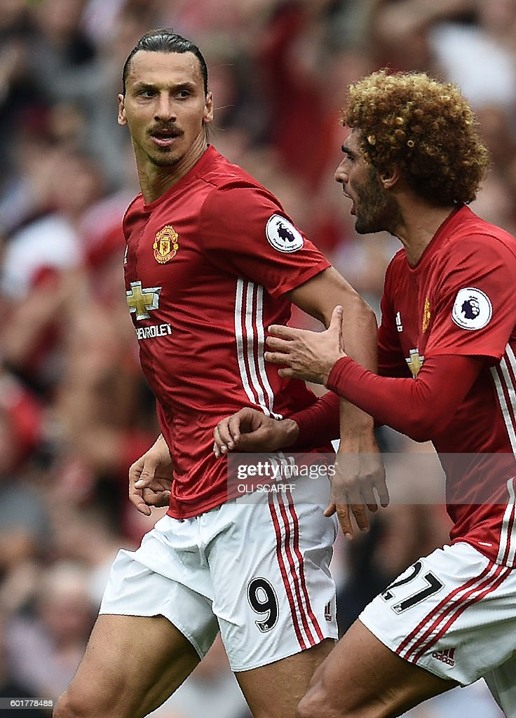 Manchester United's Swedish striker Zlatan Ibrahimovic (L) celebrates with Manchester United's Belgian midfielder Marouane Fellaini (R) after he scores their first goal during the English Premier League football match between Manchester United and Manchester City at Old Trafford in Manchester, north west England, on September 10, 2016. / AFP / Oli SCARFF / RESTRICTED TO EDITORIAL USE. No use with unauthorized audio, video, data, fixture lists, club/league logos or 'live' services. Online in-match use limited to 75 images, no video emulation. No use in betting, games or single club/league/player publications. /