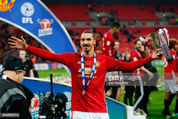 TOPSHOT Manchester United's Swedish striker Zlatan Ibrahimovic celebrates with the trophy on the pitch after their victory in the English League Cup...