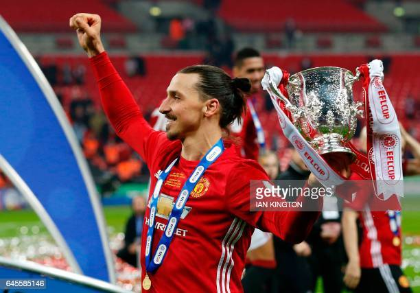 Manchester United's Swedish striker Zlatan Ibrahimovic celebrates with the trophy on the pitch after their victory in the English League Cup final...