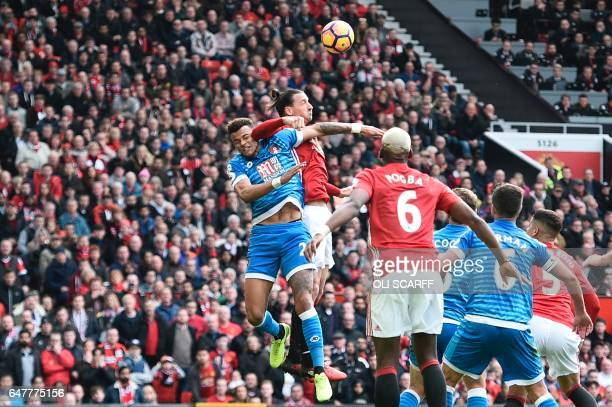 TOPSHOT Manchester United's Swedish striker Zlatan Ibrahimovic clashes in the air with Bournemouth's English defender Tyrone Mings during the English...