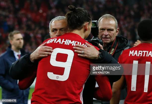 Manchester United's Swedish striker Zlatan Ibrahimovic embraces Manchester United's Portuguese manager Jose Mourinho as players celebrate on the...