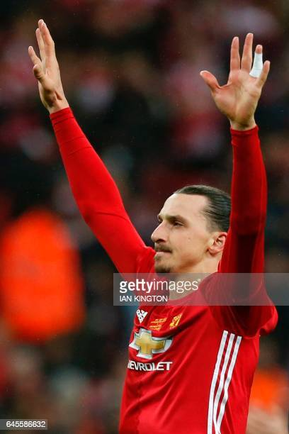 Manchester United's Swedish striker Zlatan Ibrahimovic gestures as Manchester United players celebrate on the pitch after their victory in the...